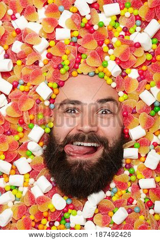 Happy bearded man showing tongue out while lying in sweets and looking at camera.