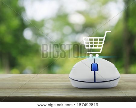 Shopping basket icon with wireless computer mouse on wooden table over blur green tree in park Shop online concept