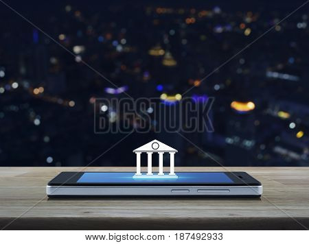 Bank icon on modern smart phone screen on wooden table over blur colorful night light city tower Mobile banking concept