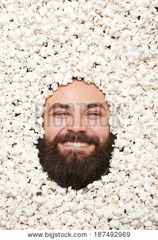 Male bearded face lying on popcorn looking at camera excitedly.