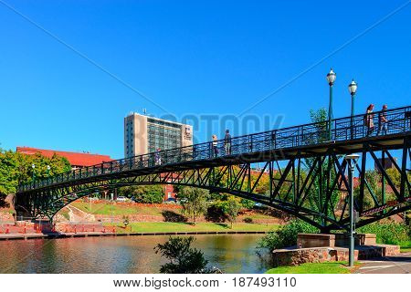 Adelaide Australia - April 14 2017: Unrecognised people walking across University Bridge through Torrens river in North Adelaide on a bright day