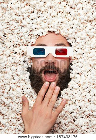 Young bearded man wearing 3-D glasses lying in popcorn and making faces while looking at camera.