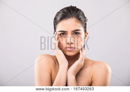 Beautiful Young Woman With Clean Fresh Skin Touch Own Face . Facial Treatment . Cosmetology , Beauty