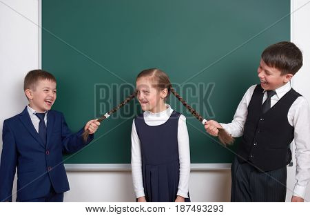 child play and having fun, boys pull the girl braids, near blank school chalkboard background, dressed in classic black suit, group pupil, education concept