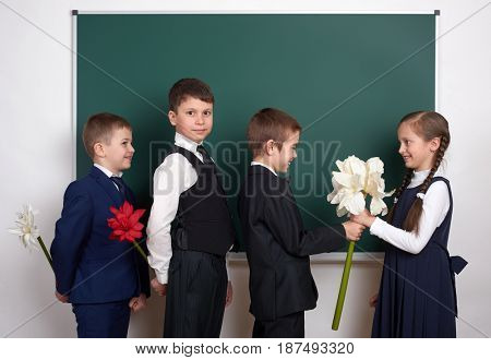 boys giving girl flowers, elementary school child near blank chalkboard background, dressed in classic black suit, group pupil, education concept