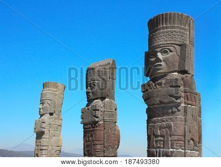 Toltec Atlantes - columns on top Pyramid of Quetzalcoatl, Tula de Allende, Hidalgo state, Mexico. UNESCO world heritage site. On blue sky background
