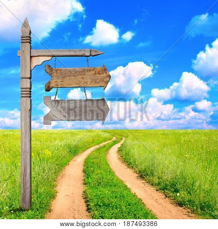 Rural summer landscape with dirt road and old wooden signboard with two wood arrows