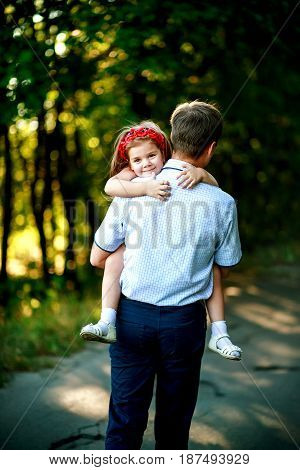 Little girl at hands of father. The baby is due to shoulder daddy. family dad and daughter walking outdoors. Man holds smiled kid.