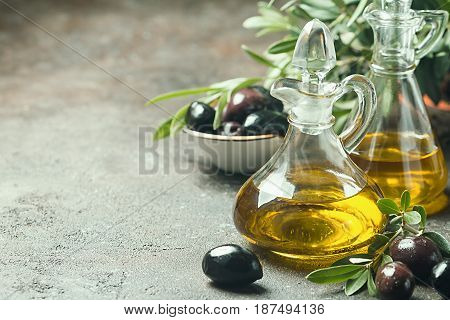 Olive oil in a glass bottle and olive branch on brown stone table