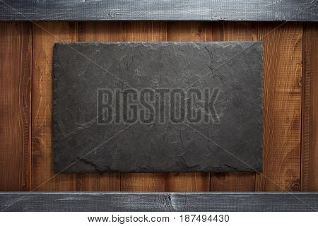 slate stone at wooden plank board background