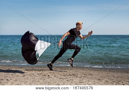 Side view of sportive man running with training parachute on seashore.