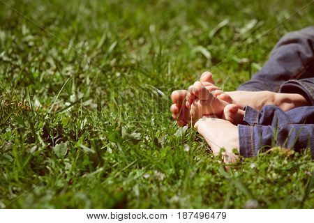 kids feet on green grass, relax in nature concept