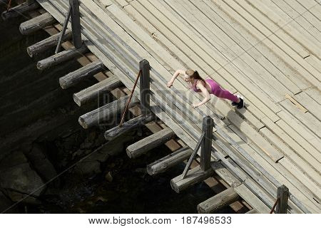 young woman doing pushups on a wooden bridge healthy lifestyle