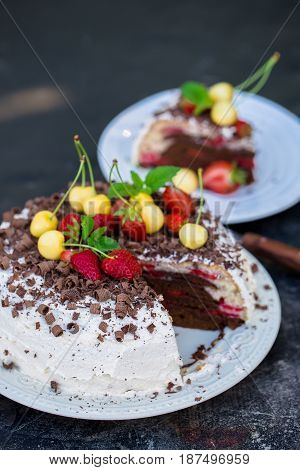 chocolate cake with fresh strawberry and yellow cherry on rustic background