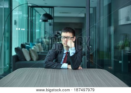 Depressed businessman is sitting alone in office