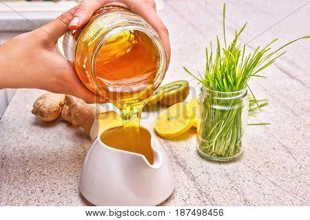 Golden liquid Organic Honey pouring from jar. Green wheat, lemon and ginger