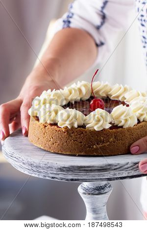Cheesecake decorated with cherry sauce with berries on a wooden cake stand