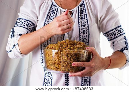 Woman's hands holding a bowl of raisins. Sweet raisins in the bowl