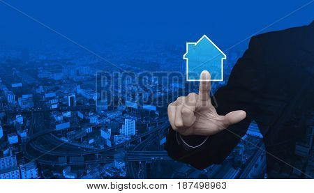 Businessman pressing house icon over modern city tower street and expressway Real estate concept