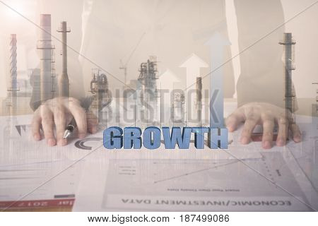 Double exposure business worker with graph growth and factory construction on desk office. concept plan investment.