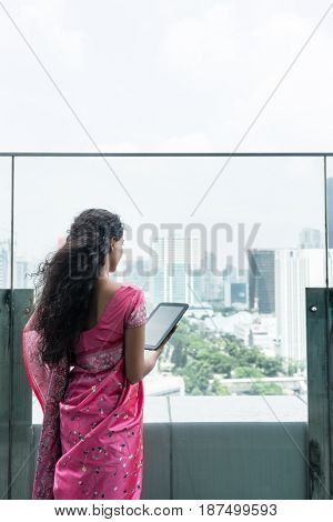 Rear view of young Indian woman looking at the city view while using a tablet Pc on a terrace in a windy day