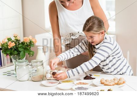 Pregnant mum and her little daughter baking together and decorating the cupcakes
