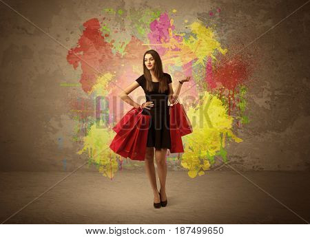 A happy young elegant woman standing with shopping bags in front of brown wall background full of colorful ink splatter concept