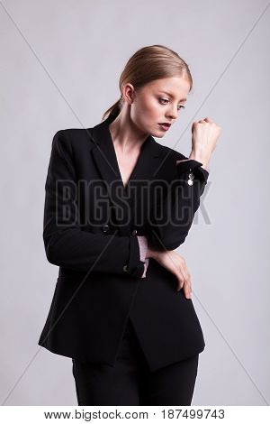 Styled gorgeous blonde in fashion suit on gray background in studio photo. Elegant blonde