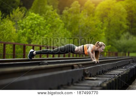 young woman doing pushups on a railway bridge healthy lifestyle