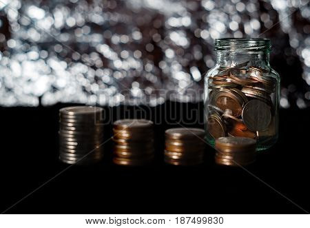 Saving money and account banking for finance business concept Coin with bottle and light bokeh on black background
