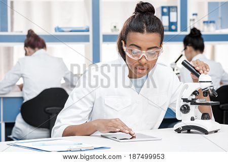 African American Scientist In Lab Coat With Microscope And Digital Tablet Working In Chemical Lab, S
