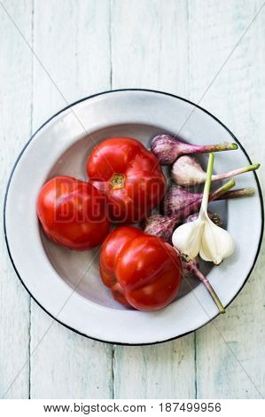 Fresh red tomato on a plate with garlic