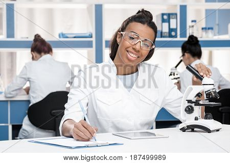 African American Scientist In Lab Coat With Clipboard, Microscope And Digital Tablet Working In Chem