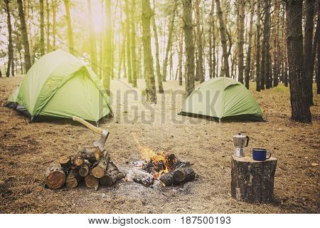 Camping in the forest tents stand around the fire.