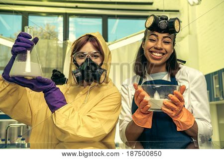 Portrait Of Women In Uniforms Holding Flask And Bowl With Reagents In Laboratory, Drugs Concept
