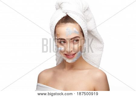 Young woman testing different masks on her face at the same time.