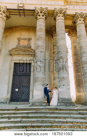 Full-length view of the newlyweds standing near the columns of the ancient building
