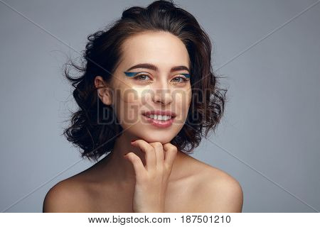 Woman with eye mask applied touching chin and looking at camera.
