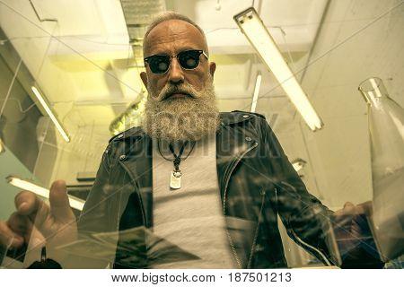 stylish grey hair man with beard sitting near glass table drugs concept