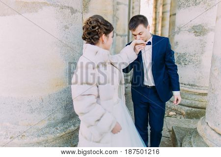 The groom is kissing the bride in the hand while standing among the ancient columns