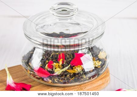 A Jar With A Black Herbal Floral Tea On A White Wooden Table.