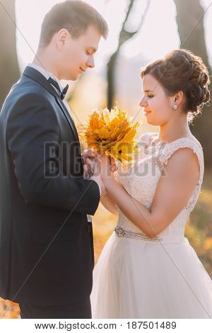 Sensitive vertical portrait of the newlyweds. The bride is holding the bouquet of yellowed leaves