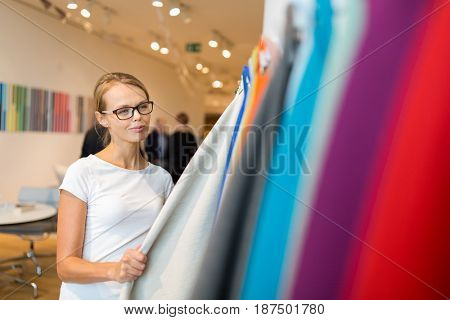 Pretty young woman  choosing the right material/color for her modern house/appartement interior (shallow DOF; color toned image)