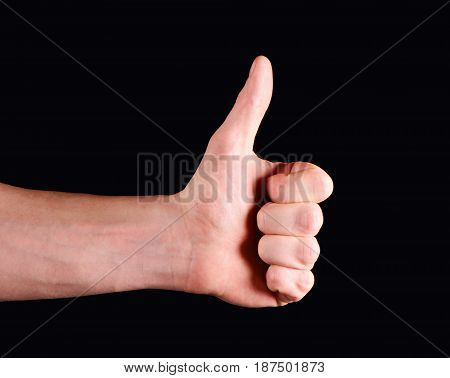 Thumbs up hand isolated on black background.