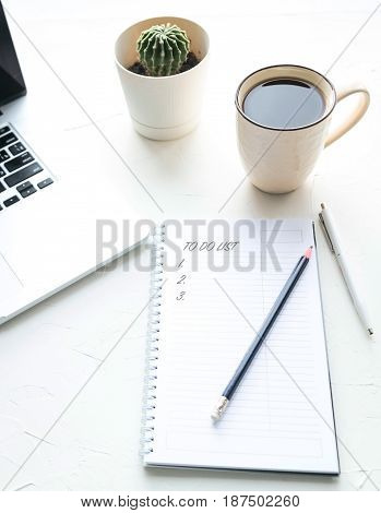 Early morning of a businessman. A cup of strong black coffee, an open notebook and a lap-top on the white wooden table.