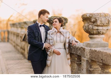 The sensitive eye contact bewtween happy newlywed couple standing near the old fence