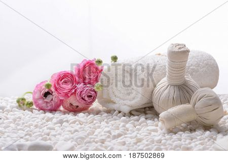 Set of ranunculus with spa ball,rolled towel on white pebbles