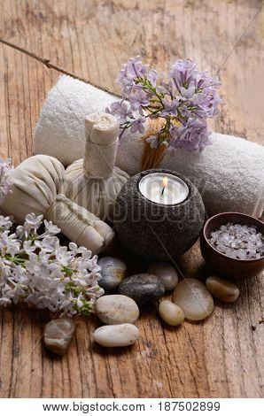 Tropical spa on old wooden with towel,candle,stones, ball,purple flower