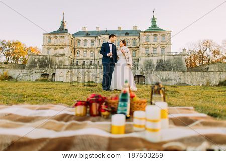 Smiling couple is spending their time and having romantic picnic in the garden of the antique castle