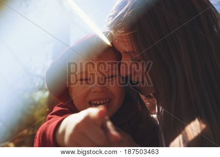 Emotional portrait of little boy looking at camera and pointing to you, while his mother hugging him. Happy smiling mom and child having fun together, playing in park.